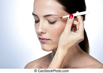 Closeup portrait of a cute young woman plucking eyebrows