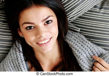 Closeup portrait of a happy woman lying on the floor with pillows. View from above