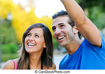 Closeup portrait of a happy young couple looking at something interesting - Copyspace