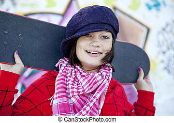 Closeup portrait of a happy young girl with skateboard and graffiti on background
