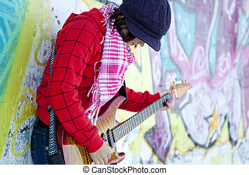 Closeup portrait of a happy young girl with guitar and graffiti on background