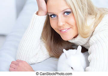 Closeup portrait of a happy young lady in relaxed pose with a rabbit