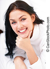 Closeup portrait of a happy young beautiful woman lying on the bed