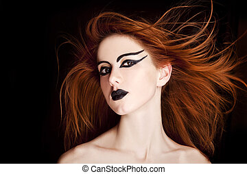Closeup portrait of a red-haired female model on black background