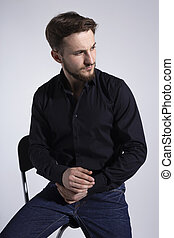 Closeup portrait of a seated bearded young man looking at the side on white background.