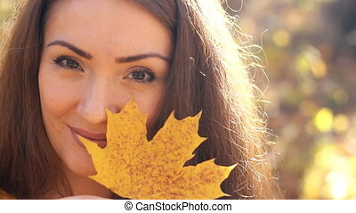 Closeup portrait of a smiling woman in the autumn sunny day...