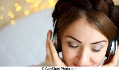Closeup portrait of a woman in headphones listening to a music song with eyes closed in the lights.
