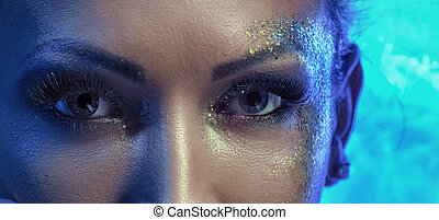 Closeup portrait of a woman with golden gust on the face