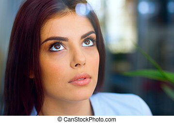 Closeup portrait of a young beautiful pensive woman
