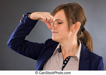 Closeup portrait of a young businesswoman holding her nose ...