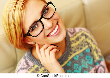 Closeup portrait of a young cheerful woman in glasses