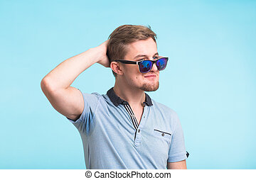 Closeup portrait of a young handsome man looking away from the camera on blue background