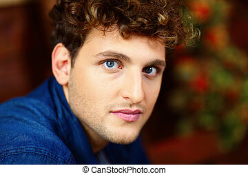 Closeup portrait of a young handsome man with curly hair