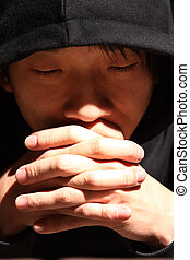 Closeup portrait of a young man praying to god