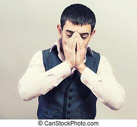 Closeup portrait of a young man praying to god