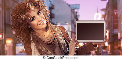 Closeup portrait of a young pretty lady with an electronic device