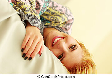 Closeup portrait of a young smiling woman lying on the bed