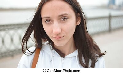 Closeup portrait of a young unhappy caucasian woman in front of a bridge near river. Happy young woman at river side thinking. Sad pensive girl looking at camera
