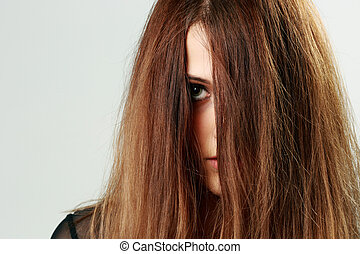 Closeup portrait of a young woman face covered with hair