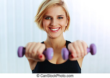 Closeup portrait of a young woman holding dumbbells