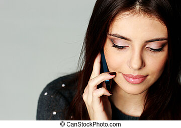Closeup portrait of a young woman talking on the phone