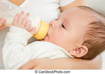 Closeup portrait of adorable baby boy sucking milk from bottle