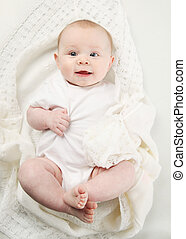 closeup portrait of adorable baby lying on a white blanket