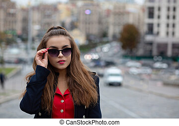 Closeup portrait of adorable brunette model wearing glasses posing in the evening city. Empty space