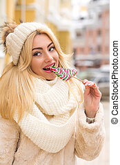 Closeup portrait of adorable young woman with natural makeup eating caramel candies