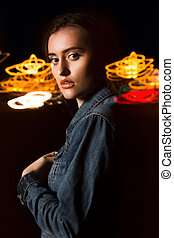 Closeup portrait of amazing young woman posing with mixed light at the street in the night