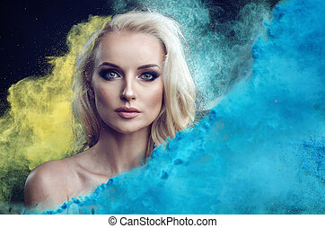 Closeup portrait of an charming blond lady among blue and yellow powder cloud
