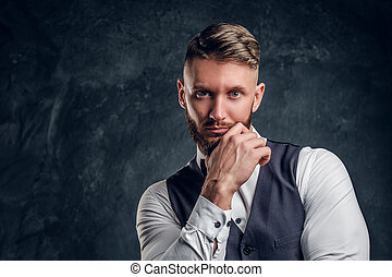 Closeup portrait of an elegantly dressed young man with stylish beard and hair holding hand on a chin and looking at a camera. Studio photo against a dark wall background