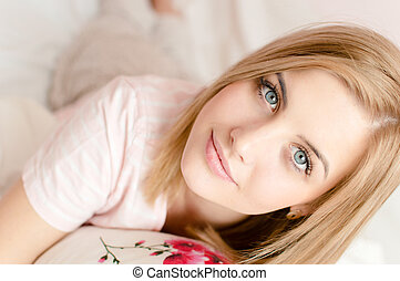 closeup portrait of attractive beautiful young blond woman with blue eyes and excellent skin in bed & looking at camera