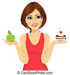 attractive woman choosing between green apple or sweet piece...