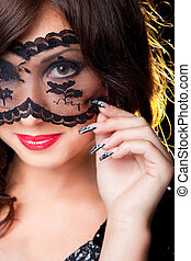Closeup portrait of attractive young brunette girl with long dark ringlets fine art manicure wearing lacy mask on her eyes