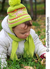 Closeup portrait of baby in hat lying on grass on autumn background outdoors