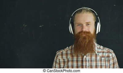 Closeup portrait of bearded young man in headphones listen...