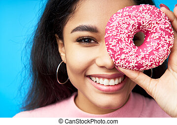 Closeup portrait of beautiful black woman and donut