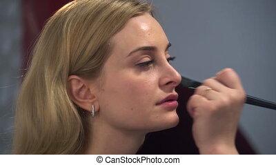 Closeup portrait of beautiful blonde woman doing make-up...