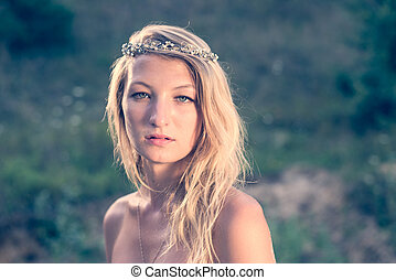 closeup portrait of beautiful blonde young woman wearing silver diadem looking at camera with bare shoulders. head shot on green summer outdoors copy space background.