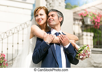beautiful bride hugging grooms shoulders on street at sunny day