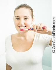 Closeup portrait of beautiful brunette woman brushing teeth