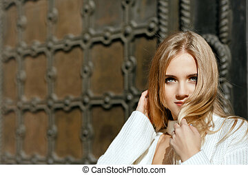 Closeup portrait of beautiful model with natural makeup posing near metal wrought door. Space for text