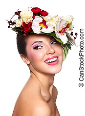 closeup portrait of beautiful sexy smiling brunette caucasian young woman model with glamour lips,bright makeup. With colorful flowers on head