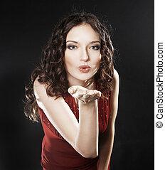 closeup. portrait of beautiful woman in red dress sending a kiss.