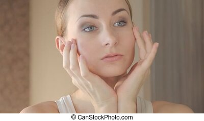 Closeup portrait of beautiful woman touching face skincare...