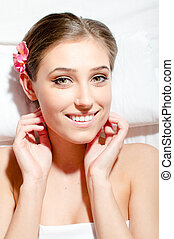 closeup portrait of beautiful young woman during spa treatments happy smiling & looking at camera on white background