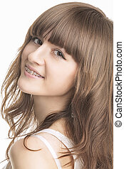 Closeup Portrait of Beautiful Young Woman With Brackets on Teeth. Isolated Over White Background. Vertical Image