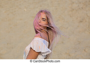 Closeup portrait of blonde girl posing covered with dry Holi paint at the desert
