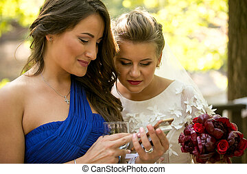 portrait of bride and bridesmaid using mobile phone